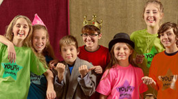 Cheerful group of child actors stand together and smile at the camera