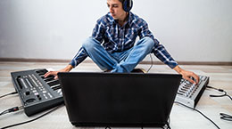 young man with  laptop and two synthesizers sitting on the floor. the process of creating electronic music